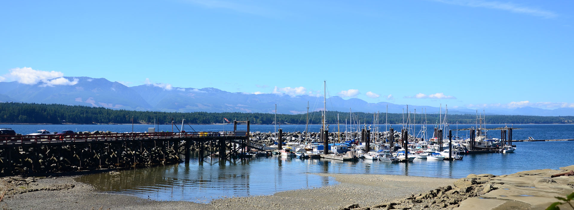 small marina with sailboats in a bay of ocean water, mountains in the distance