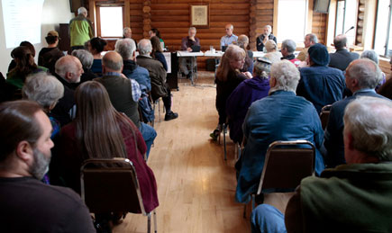 Group of locals in a log building conducting a town hall meeting