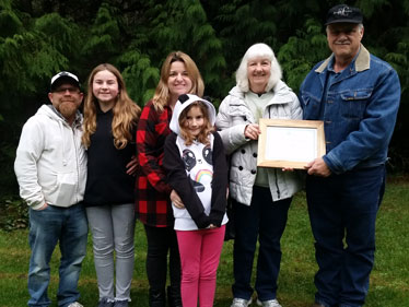 a three generation family of six stands side by side outside the eldest man and woman holding a framed award