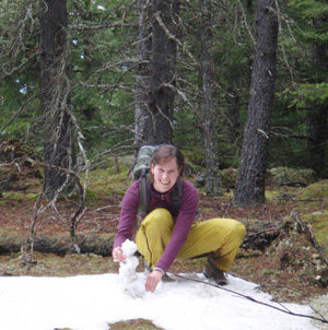 A young woman in yellow work pants and a purple top crouches smiling beside a tiny snowman in the clearing of a woods