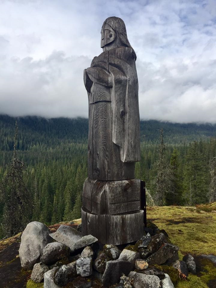 old totem pole statue on the cliff with trees in the valleys below
