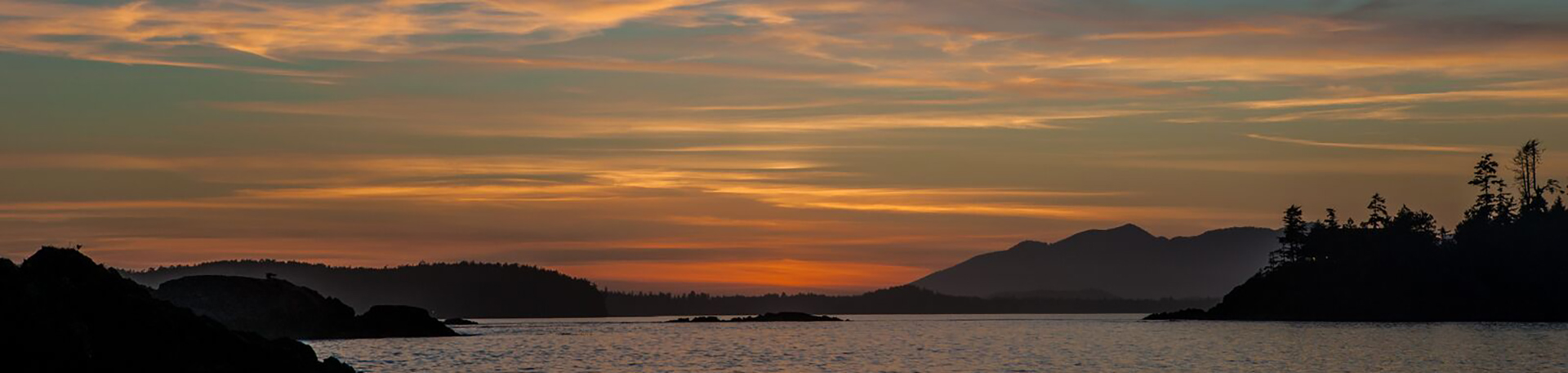 Orange and peach sunset over islands in an inlet