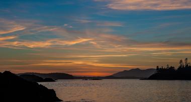 Orange sunset down a blue sky over an ocean inlet