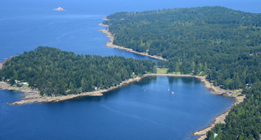 Aerial photograph of tree-covered Gabriola island and seashores in a deep blue ocean