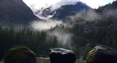 Three large boulders symmetrically placed on a cliff edge looking out over a misty forest and cloud covered mountains