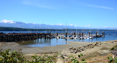 A small marina with sailboats in a sandy bay with the ocean and island mountain ranges in the background