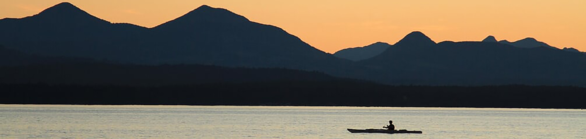 kayaker at sunset with shadowed mountain range in the distance