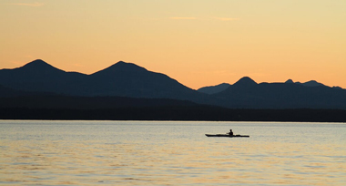 A kayaker drifting on the ocean in an orange sunset with shadowed mountains in the distance