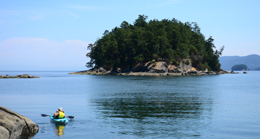 A kayaker in a blue boat and yellow jacket drifts next to a rock outcrop near a small tree covered island in the ocean