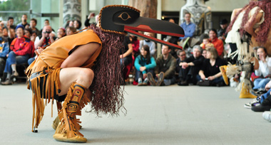 First Nations dancer in a raven mask crouches in the middle of a circle made by a crowd of onlookers