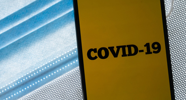 a close up of a blue and white face mask with a yellow Covid-19 sticker