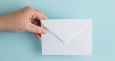 a hand holding a white envelope in front of a pale blue wall