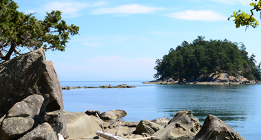 Rocky outcrop over the ocean under a blue sky facing a small island covered in green trees.
