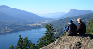 An older man and woman on a rocky viewpoint looking down at the ocean from Salt Spring Island