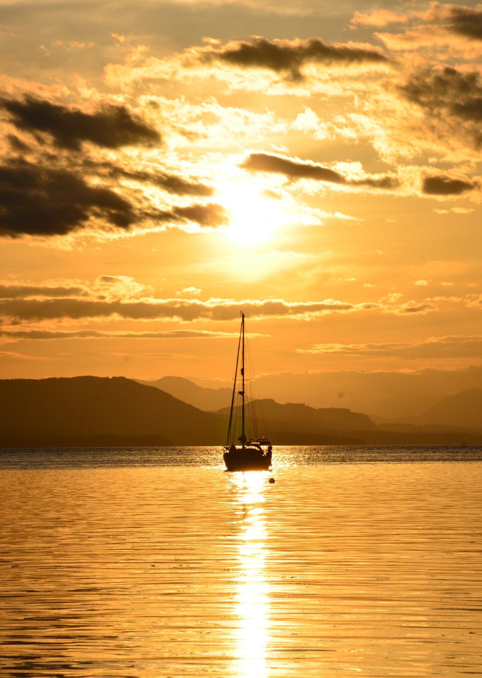 Sailboat in the distance heading towards islands under the golden glow of a sunset
